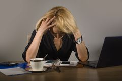 Jeune femme frustrante et soumise à une contrainte d'affaires pleurant au bureau fonctionnant avec l'ordinateur portable accablé  photographie stock