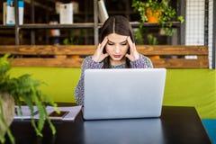 Jeune femme frustrante travaillant au bureau devant l'ordinateur portable souffrant des maux de tête quotidiens chroniques Photo libre de droits