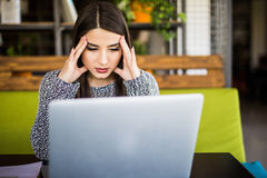 Jeune femme frustrante travaillant au bureau devant l'ordinateur portable souffrant des maux de tête quotidiens chroniques Photographie stock libre de droits