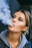 Jeune femme fumant la cigarette électronique images stock
