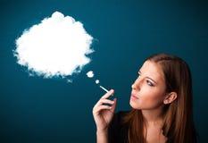 Jeune femme fumant la cigarette malsaine avec de la fumée dense Images libres de droits