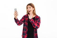 Jeune femme gaie à l'aide du téléphone portable avec l'ondulation d'écouteurs Photographie stock libre de droits