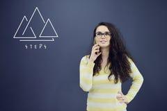 Jeune femme gaie avec le fond avec le graphique, la flèche et les icônes tirés de gestion Photographie stock libre de droits