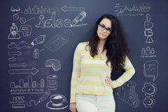 Jeune femme gaie avec le fond avec le graphique, la flèche et les icônes tirés de gestion Images libres de droits