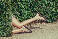 Jeune femme gaie avec les jambes sexy avec le tatouage, dans l'herbe verte, dehors Photographie stock