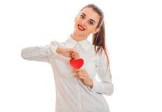 Jeune femme gaie avec les lèvres rouges préparant pour célébrer le jour de valentines avec le symbole de coeur dans le studio d'i Photographie stock