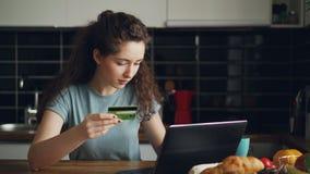 Jeune femme gaie ayant des achats en ligne utilisant l'ordinateur portable et carte de crédit tandis que prenez le petit déjeuner banque de vidéos