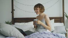 Jeune femme gaie ayant la causerie visuelle avec des amis employant l'appareil-photo d'ordinateur portable tout en se reposant su Images stock