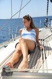 Jeune femme gaie détendant sur la croisière de bateau à voile Images stock