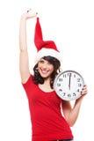 Jeune femme gaie dans l'horloge de fixation de chapeau de Santa Photos libres de droits