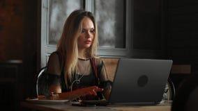 Jeune femme gaie de sourire amicale attirante dans des affaires jaunes élégantes d'un manteau sur l'Internet par l'appel visuel u banque de vidéos