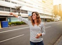 Jeune femme gaie grêlant une cabine sur la rue de ville Image stock