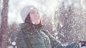 Jeune femme gaie jetant la neige en l'air pelucheuse en parc banque de vidéos