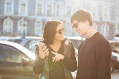 Jeune femme gaie marchant dehors avec le frère à l'aide du téléphone Photographie stock