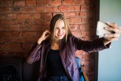 Jeune femme gaie posant tout en se photographiant sur l'appareil-photo futé de téléphone pour une causerie avec ses amis, hanches Photographie stock