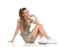 Jeune femme gaie s'asseyant sur un plancher Photographie stock libre de droits