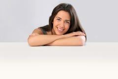 Jeune femme gaie se penchant sur la table Photos stock