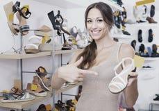Jeune femme gaie se tenant avec la chaussure choisie Photos libres de droits