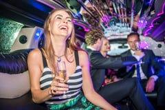 Jeune femme gaie tenant la cannelure de champagne tandis que célébrité d'amis Photographie stock