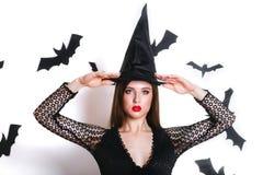 Jeune femme gothique heureuse dans le costume de Halloween de sorcière avec le chapeau se tenant et souriant au-dessus du fond bl photos libres de droits