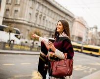Jeune femme grêlant un taxi sur la rue dans la ville Images stock