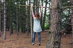 Jeune femme grimpant à un arbre Photos libres de droits