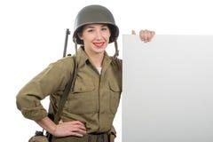 Jeune femme habill?e dans l'uniforme militaire de l'Am?ricain ww2 montrant l'enseigne vide vide photo stock