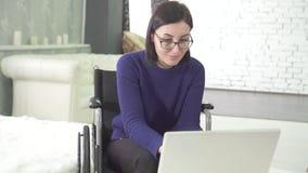 Jeune femme handicapée avec des verres dans une chaise de fauteuil roulant avec un ordinateur portable à la maison, souriant clips vidéos