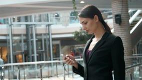 Jeune femme heureuse à l'aide du téléphone intelligent dans le centre commercial Indépendante de femme d'affaires avec le smartph Photo stock