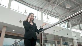 Jeune femme heureuse à l'aide du téléphone intelligent dans le centre commercial Indépendante de femme d'affaires avec le smartph Photographie stock libre de droits