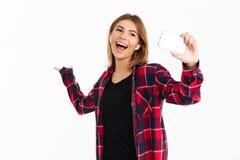Jeune femme heureuse à l'aide du téléphone portable avec des écouteurs Image stock