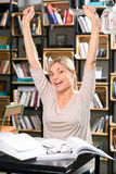 Jeune femme heureuse à la bibliothèque photos stock