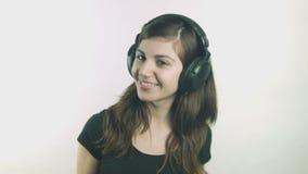 Jeune femme heureuse écoutant la musique sur des écouteurs clips vidéos