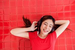 Jeune femme heureuse étendue sur le plancher rouge en musique de écoute par l'intermédiaire He Photographie stock