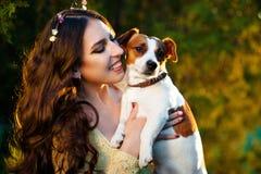 Jeune femme heureuse étreignant et ayant l'amusement avec son Jack Russell Terrier dehors Photo stock