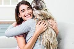 Jeune femme heureuse étreignant l'ami féminin Photographie stock