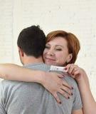Jeune femme heureuse étreignant le mari tenant l'essai de grossesse de résultat positif attendant un bébé Photo libre de droits