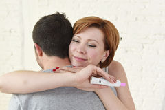 Jeune femme heureuse étreignant le mari tenant l'essai de grossesse de résultat positif attendant un bébé Photos libres de droits