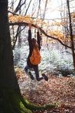 Jeune femme heureuse accrochant sur l'arbre en bois avec le sac à dos orange Fille drôle dupant autour sur un fond de forêt images libres de droits
