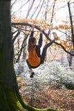 Jeune femme heureuse accrochant sur l'arbre en bois avec le sac ? dos orange Fille dr?le dupant autour sur un fond de for?t images libres de droits