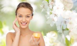 Jeune femme heureuse appliquant la crème à son visage photos libres de droits