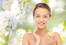 Jeune femme heureuse appliquant la crème à son visage Image libre de droits