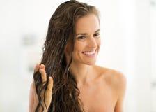Jeune femme heureuse appliquant le masque de cheveux dans la salle de bains images libres de droits
