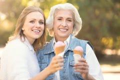 Jeune femme heureuse appréciant la crème glacée avec la vieille mère dehors Photographie stock libre de droits