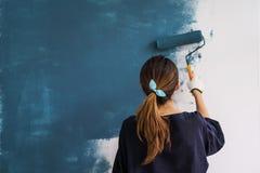 Jeune femme heureuse asiatique peignant le mur intérieur Photographie stock libre de droits