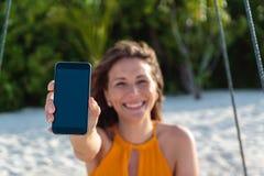 Jeune femme heureuse assise sur une oscillation montrant un ?cran vertical de t?l?phone Sable et jungle blancs comme fond photo stock