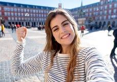 Jeune femme heureuse attirante prenant une photo d'individu Dans le concept d'extérieur de loisirs de tourisme image libre de droits