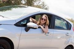 Jeune femme heureuse attirante s'asseyant dans l'été de voiture photo stock
