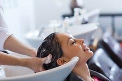 Jeune femme heureuse au salon de coiffure Image libre de droits