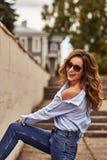 Jeune femme heureuse avec de longs cheveux bruns dans des lunettes de soleil, blues-jean, promenades bleues de chemise par la vie image libre de droits